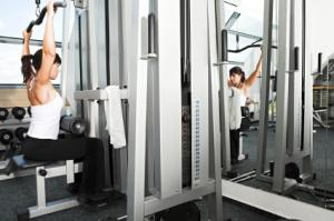 woman about to perform lat pulldowns at gym