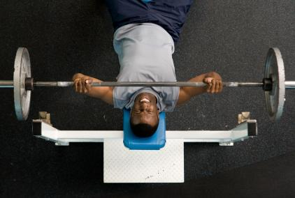 man performing bench press with free weights