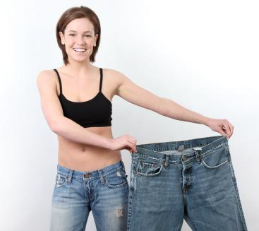 woman who has lost weight holding up a pair of large jeans